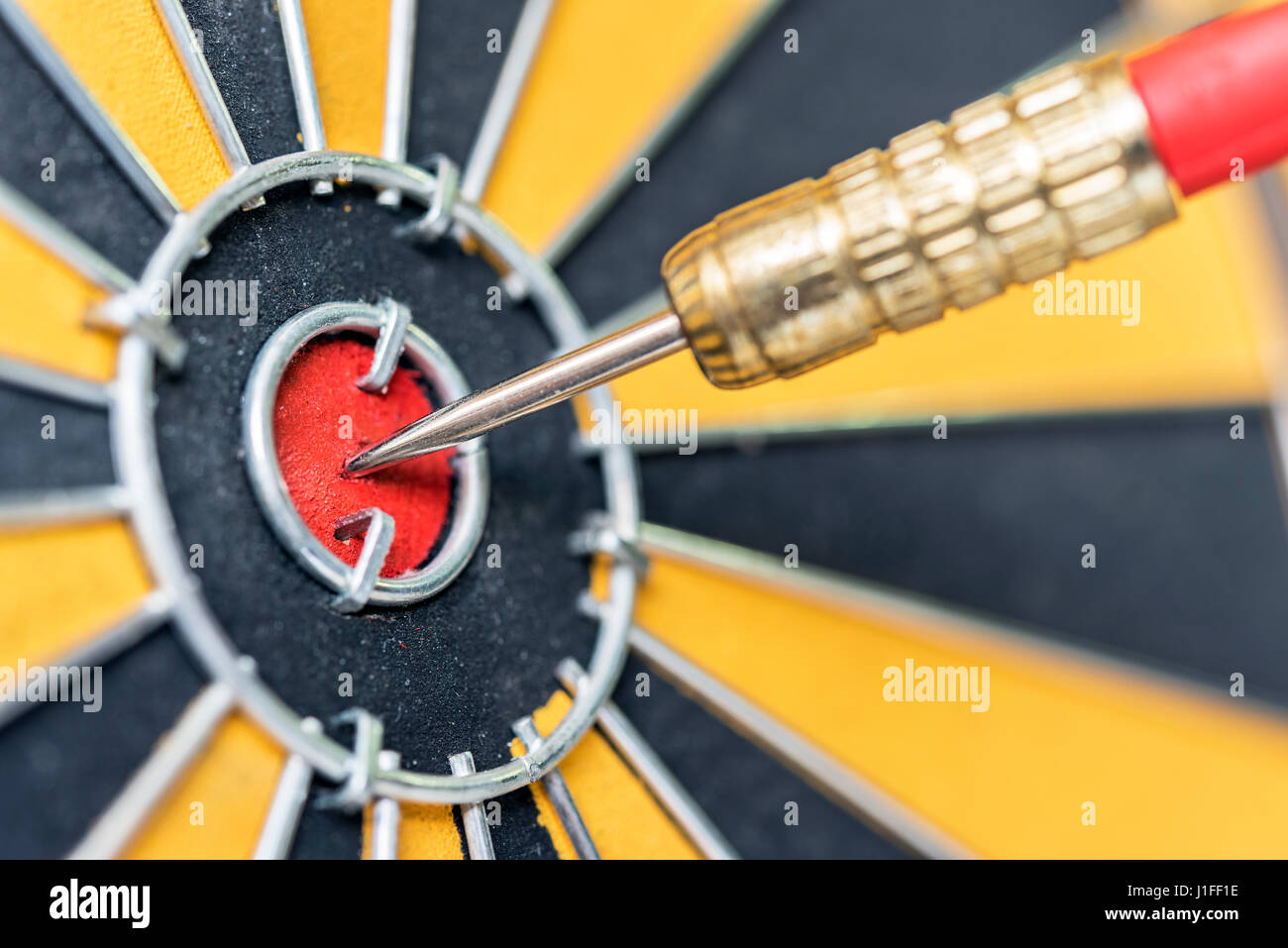 closeup dart arrow hitting in target bullseye of dartboard, business data integration solutions and success concept - Stock Image