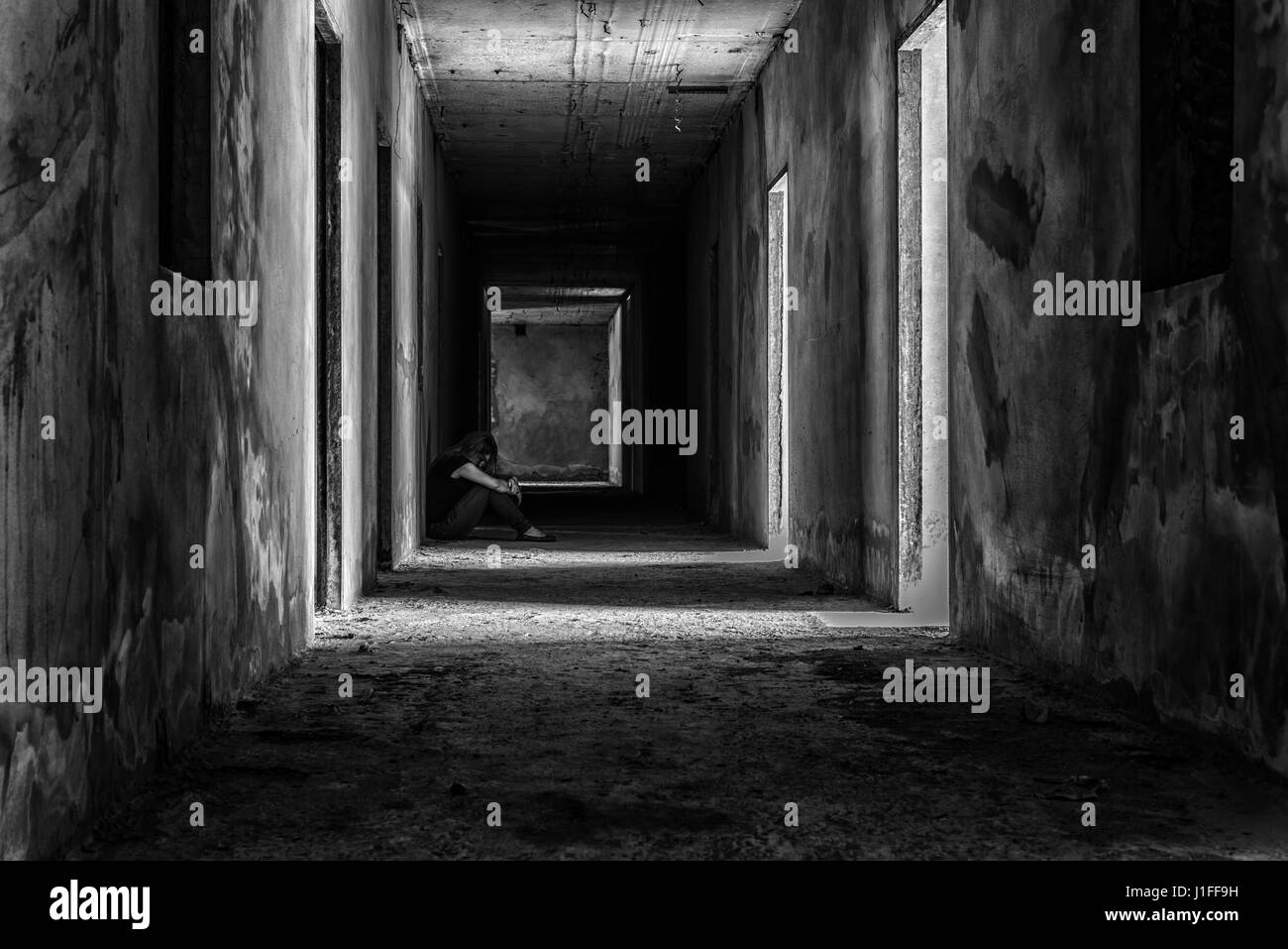 depressed woman sitting on walkway in creepy abandoned building, darkness concept - Stock Image