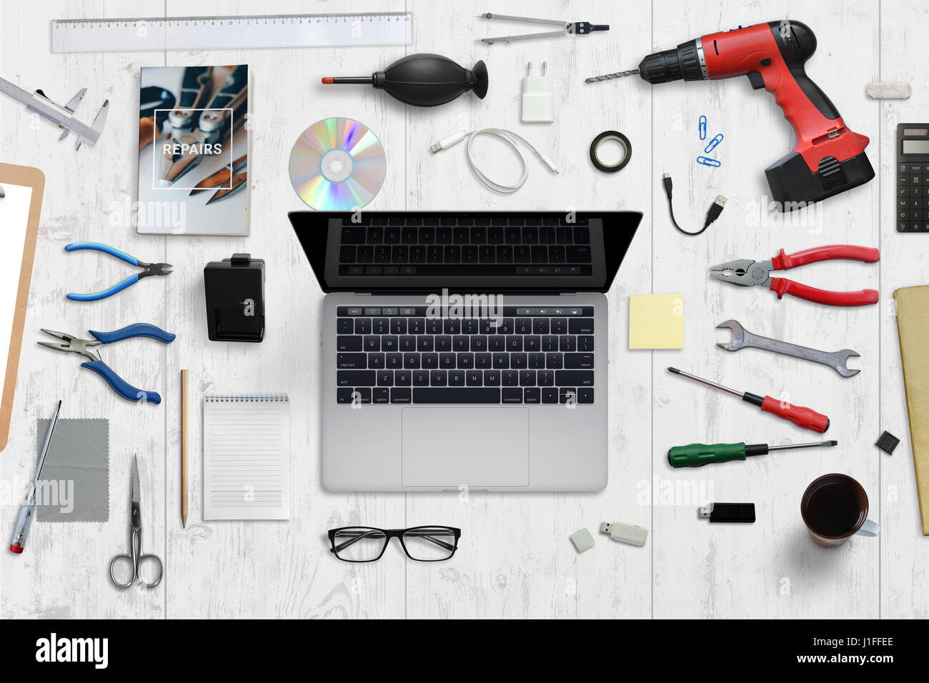 Computer hardware service desk. Laptop with blank screen surrounded with repair tools. Top view. - Stock Image