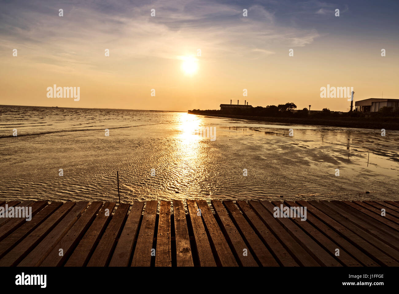 wooden bridge with beautiful sunset background above the sea, warm tone - Stock Image