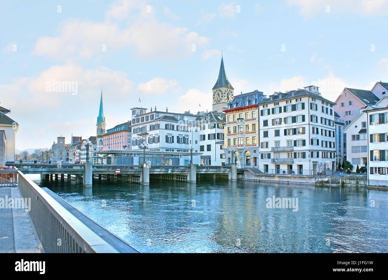 The Limmat quay overlooks the bridges and historic neighborhoods of the city center, the tall spires of Fraumunster - Stock Image