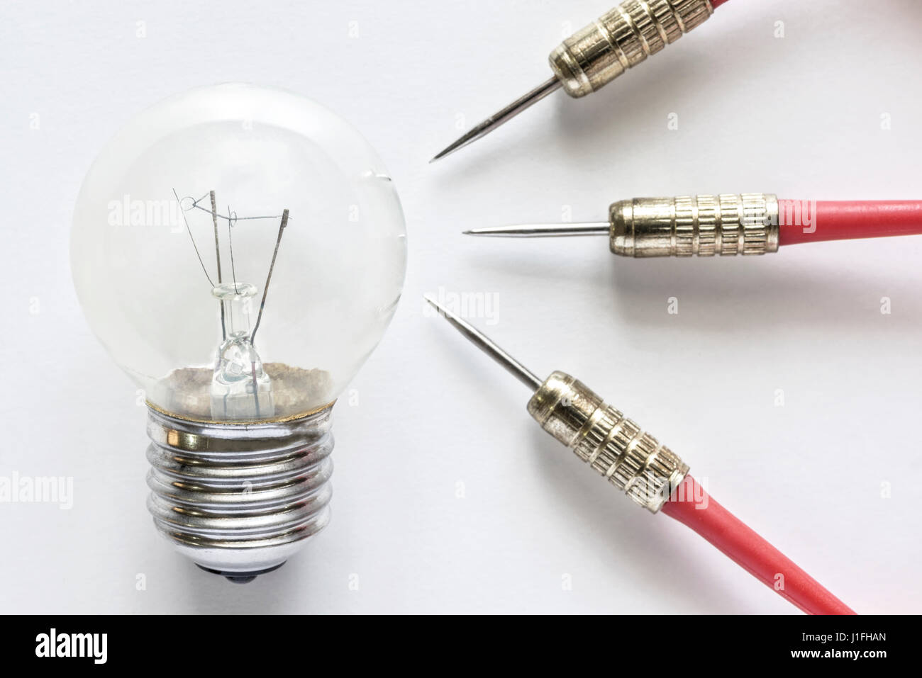 Closeup bulb lamp with three dart on white background, idea and business success concept - Stock Image
