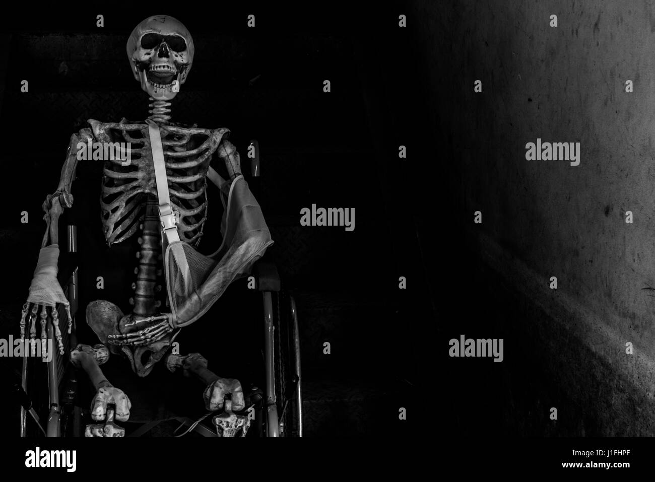 Abandoned hospital building ghost living place with human skeleton sitting in wheelchair, darkness horror and halloween - Stock Image