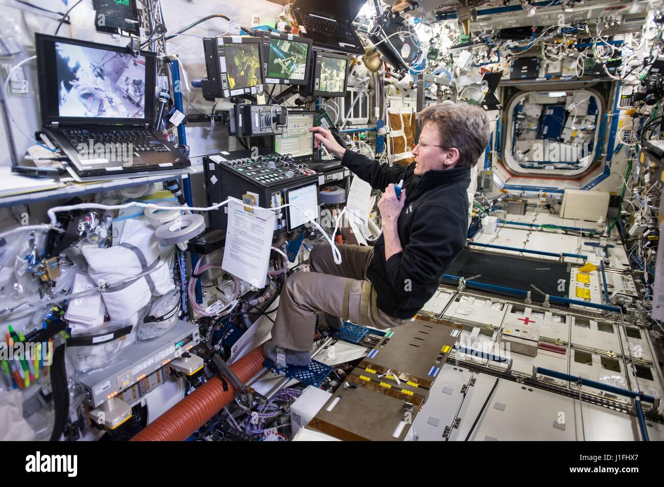 NASA Expedition 50 prime crew member American astronaut Peggy Whitson controls the Canadarm2 robotic arm from aboard - Stock Image