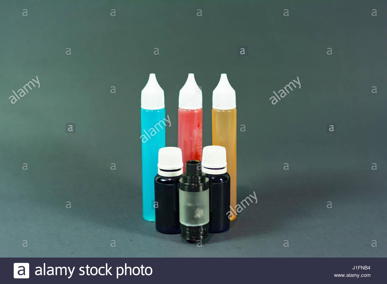e cigarette liquid bottles on isolated black background photograph - Stock Image