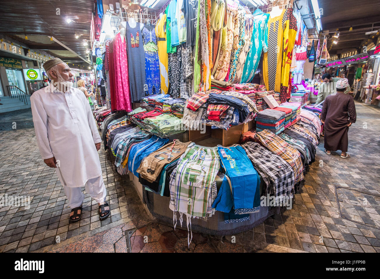 Muscat, Oman - Souq Muttrah Man looks at clothing for sale in market