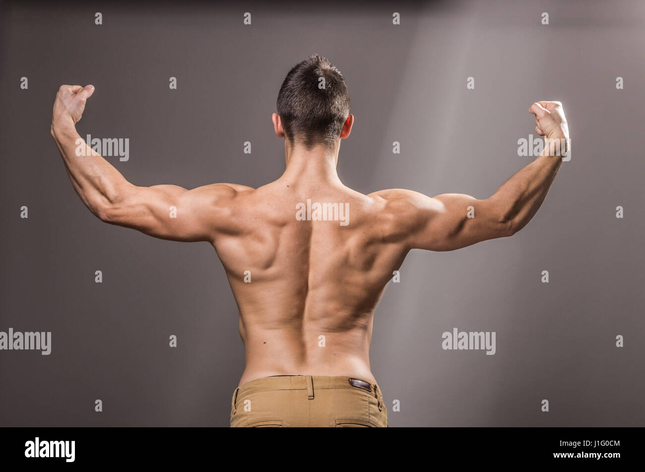 rear view, back muscles bodybuilder, young adult man posing, arms ...