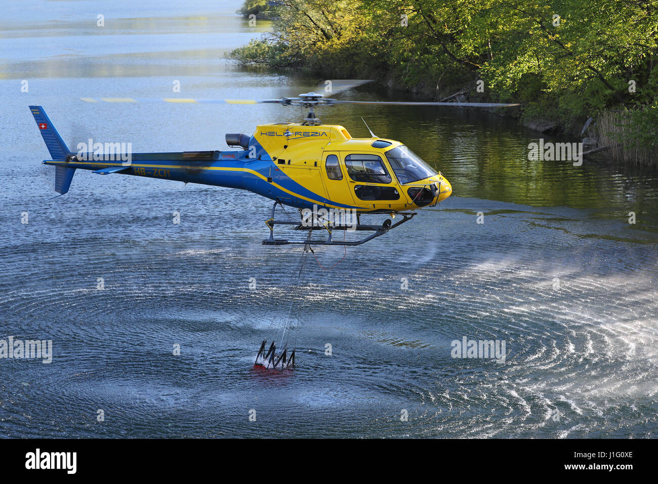 Fire fighting efforts are under way with helicopters to put out forest fires above Gordola, Ticino, Switzerland, - Stock Image