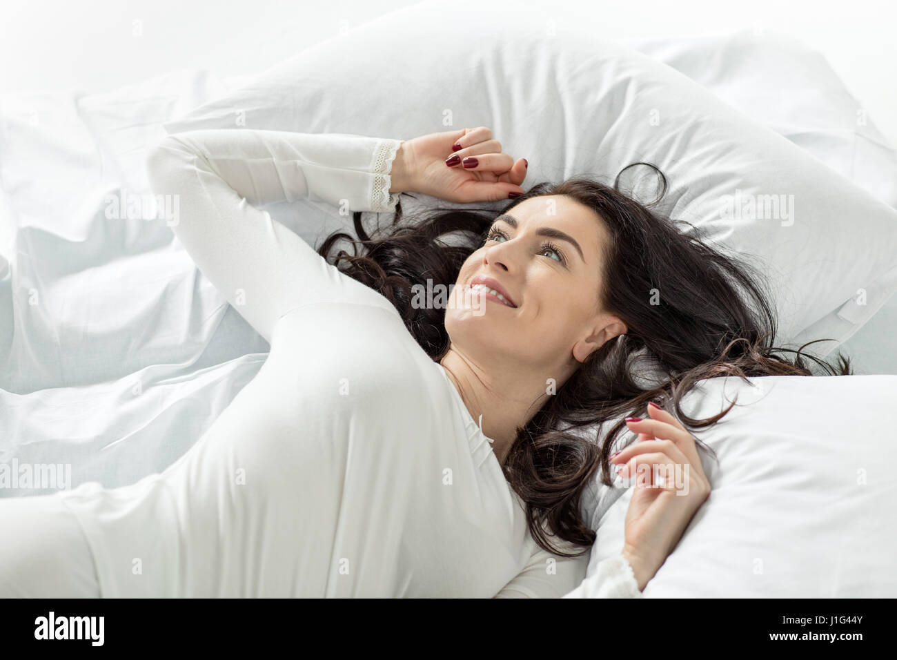 attractive woman in white sleepwear awakening in bed at home - Stock Image
