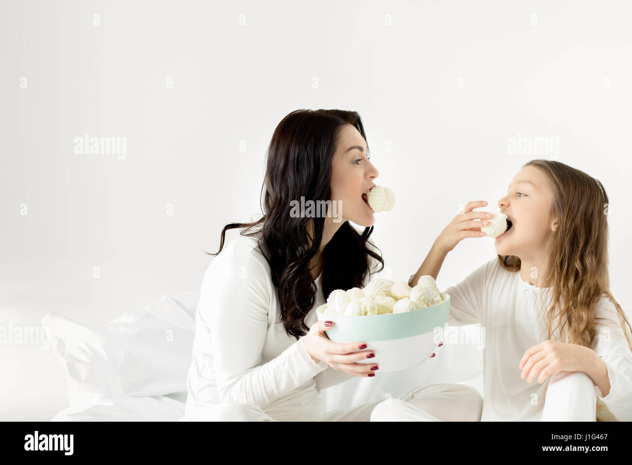 Adorable daughter and mother sitting on bed and eating marshmallows at home - Stock Image