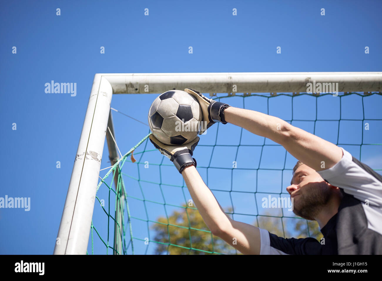 goalkeeper with ball at football goal on field - Stock Image