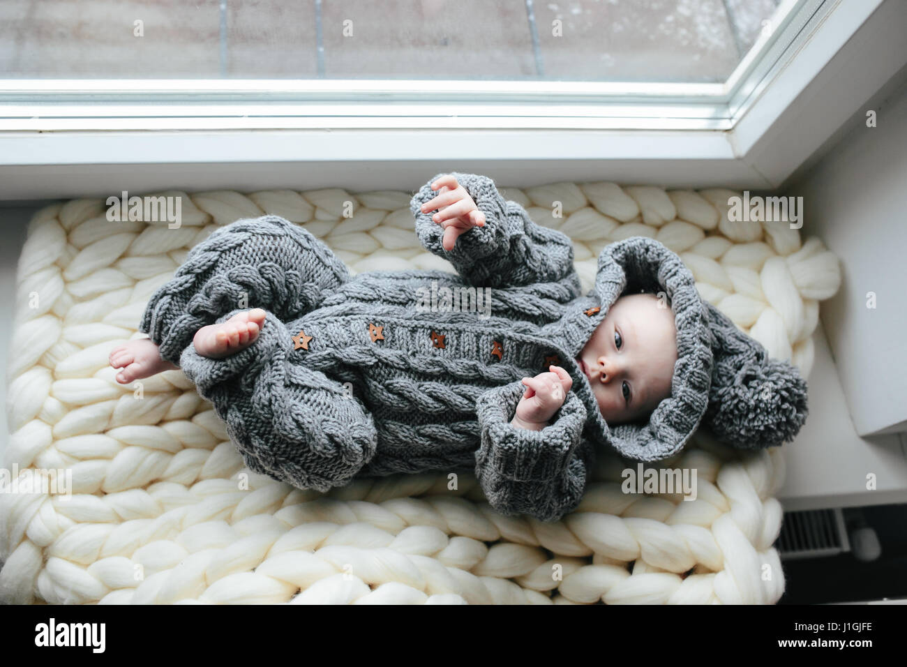 Small baby in knitted clothes - Stock Image