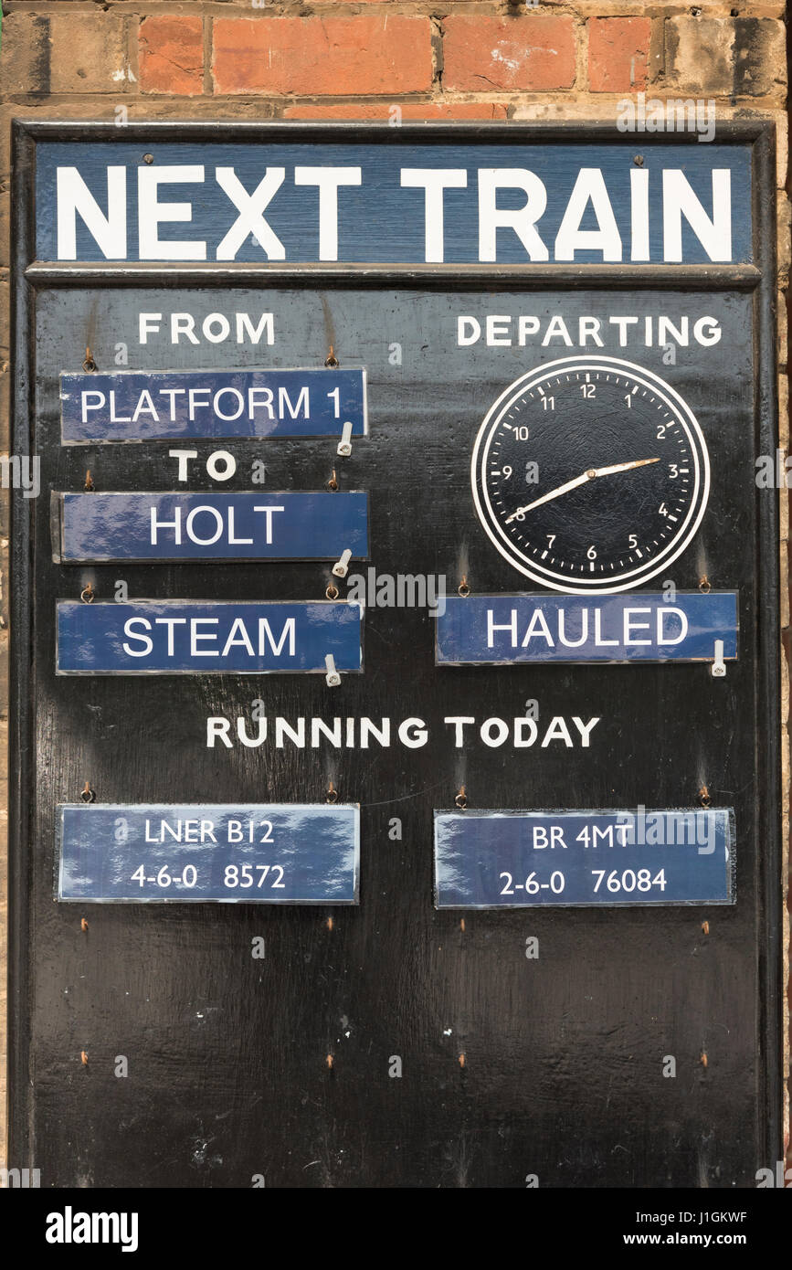 A sign on the Poppy Line steam train platform at Sheringham Norfolk showing arrival and departure times and the - Stock Image