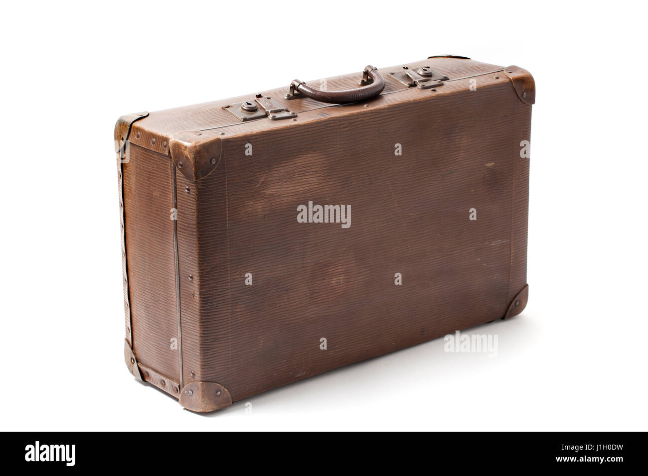 Closed obsolete antiquated and used suitcase stands isolated on white background. - Stock Image
