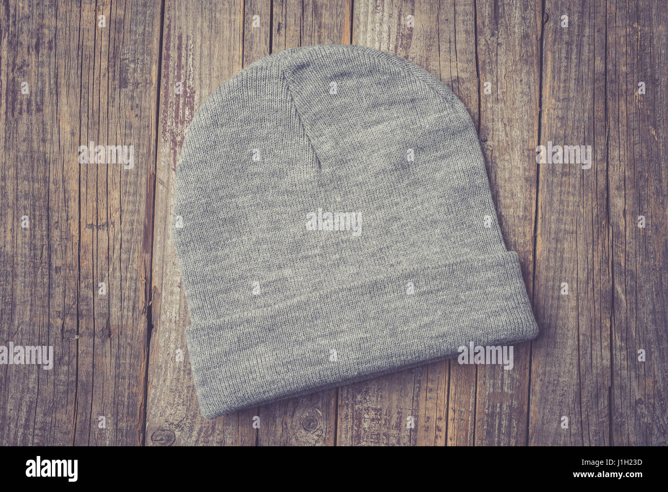 Winter cap on an old wooden table. Close up - Stock Image