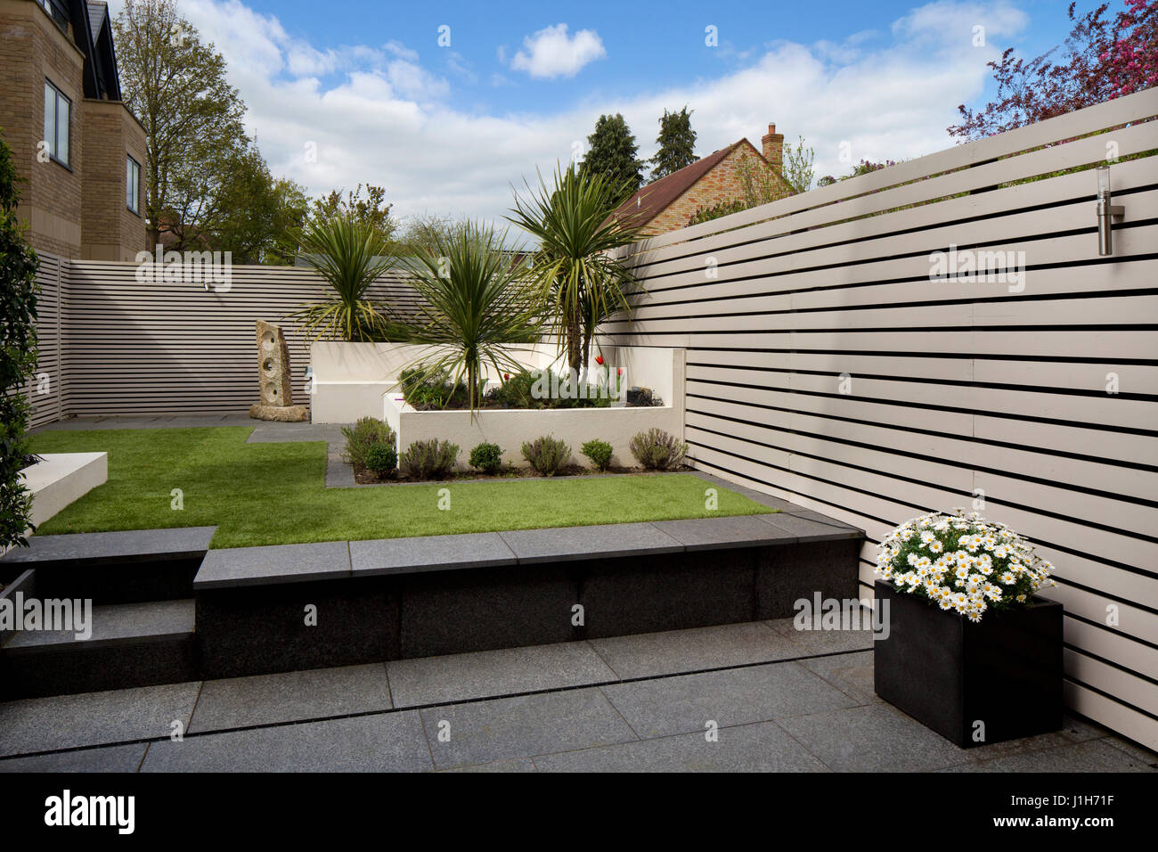 Modern Contemporary English garden with Wooden slated painted screen fence, fake grass and granite paving - Stock Image
