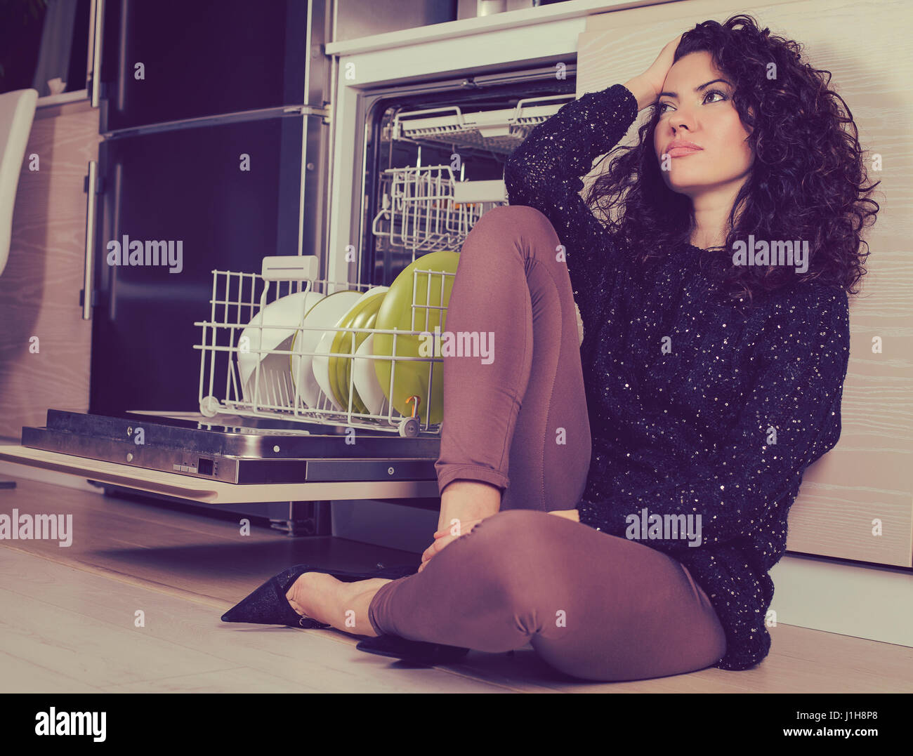 Stressed woman relaxing in the kitchen sitting on a floor Stock Photo