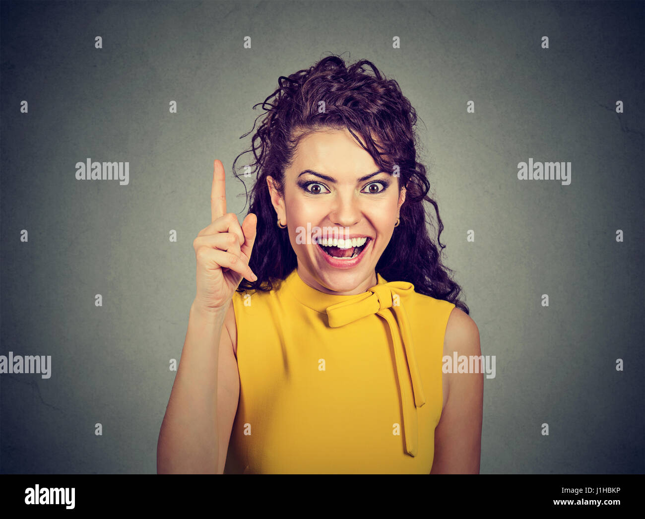 Attractive woman pointing finger up has an idea - Stock Image