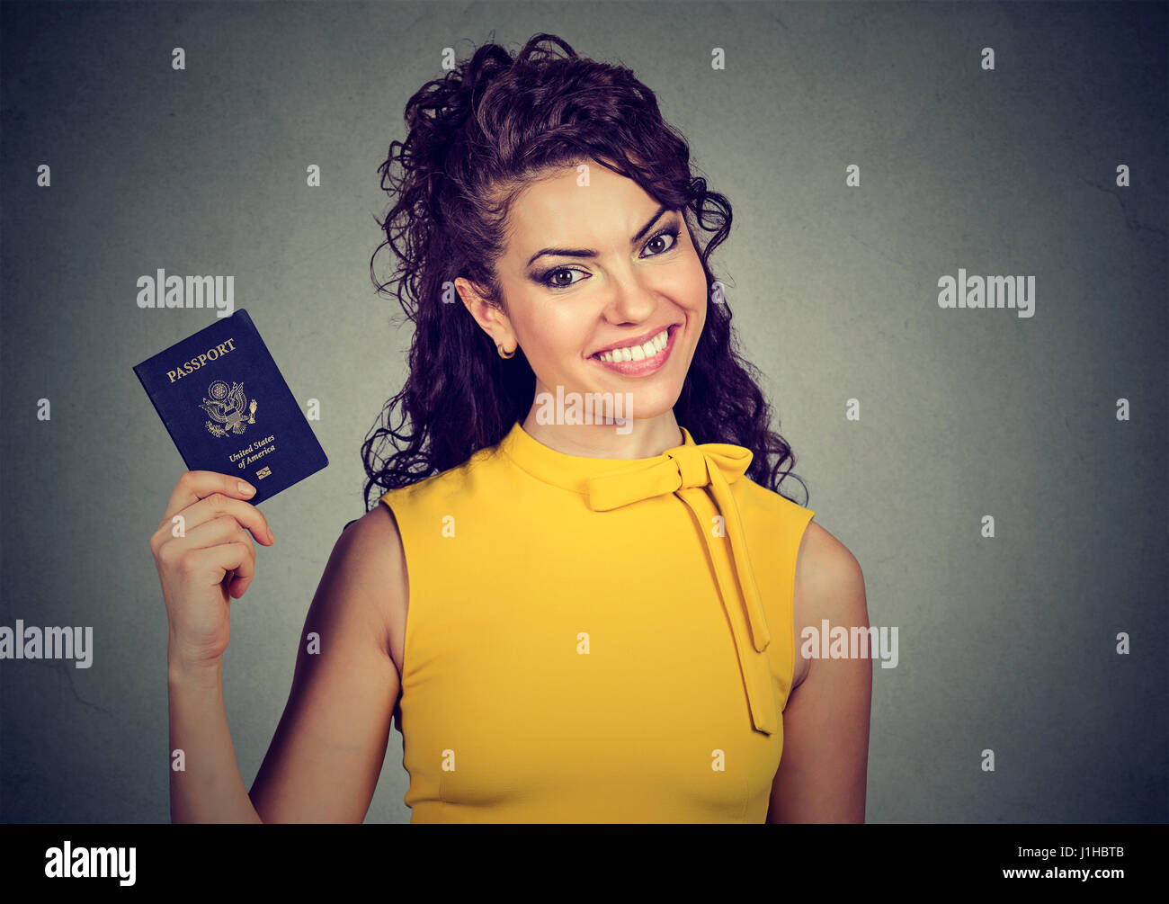 Portrait attractive excited woman with USA passport isolated on gray wall background. Positive human emotions face - Stock Image