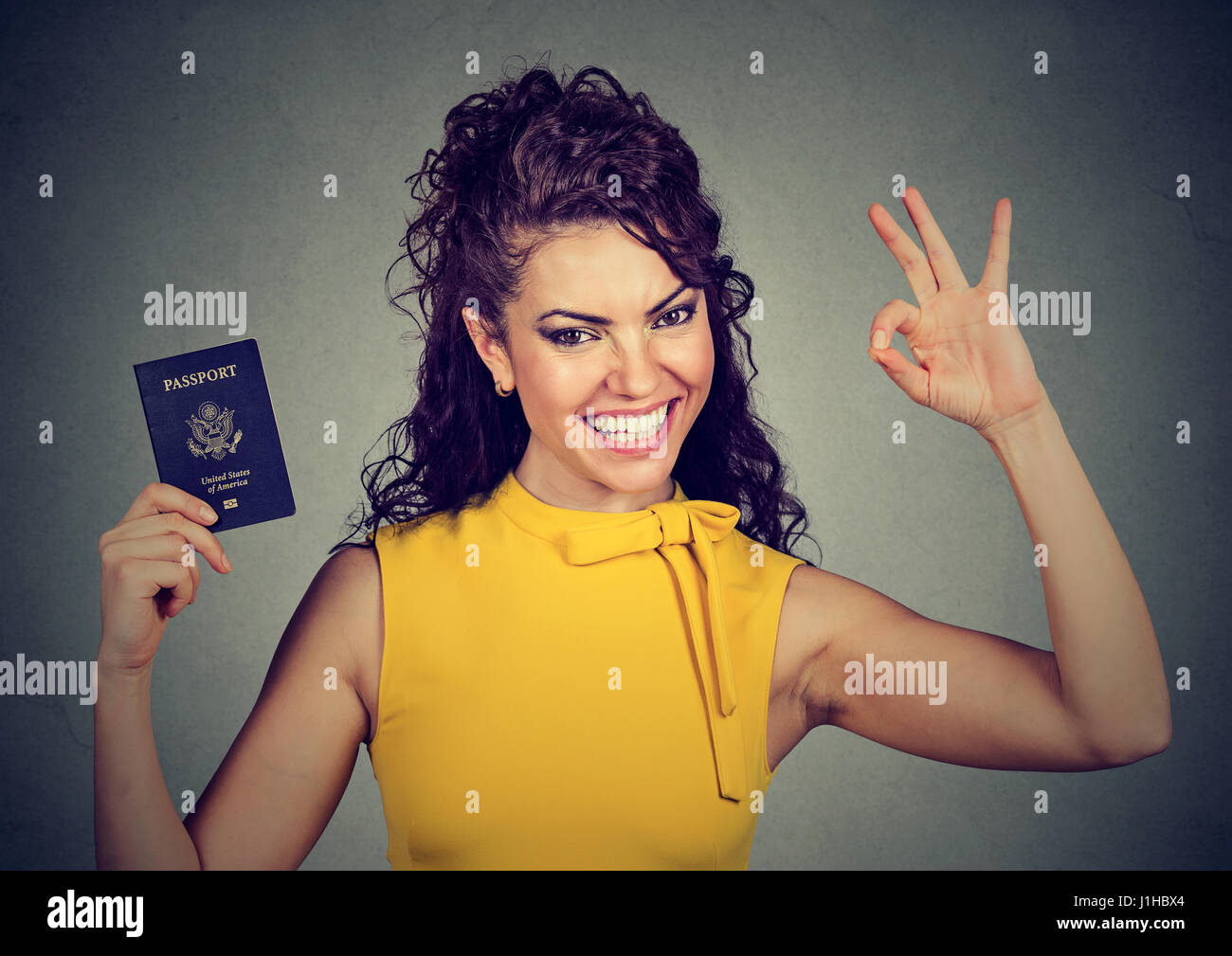 Portrait attractive young happy woman with USA passport giving ok sign isolated on gray wall background. Positive - Stock Image