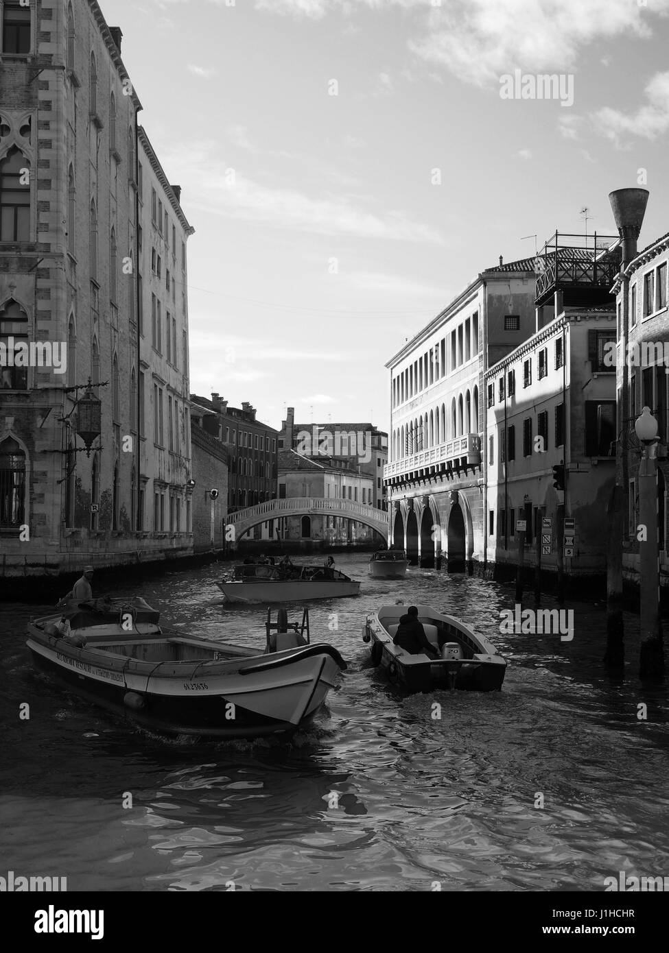 Canal in venice with bridge and two passing boats - Stock Image