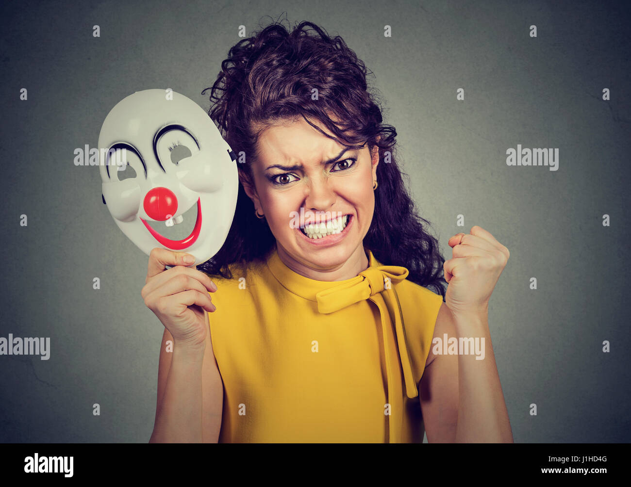 Portrait angry screaming woman taking off a clown mask expressing happiness isolated on gray wall background. Human Stock Photo