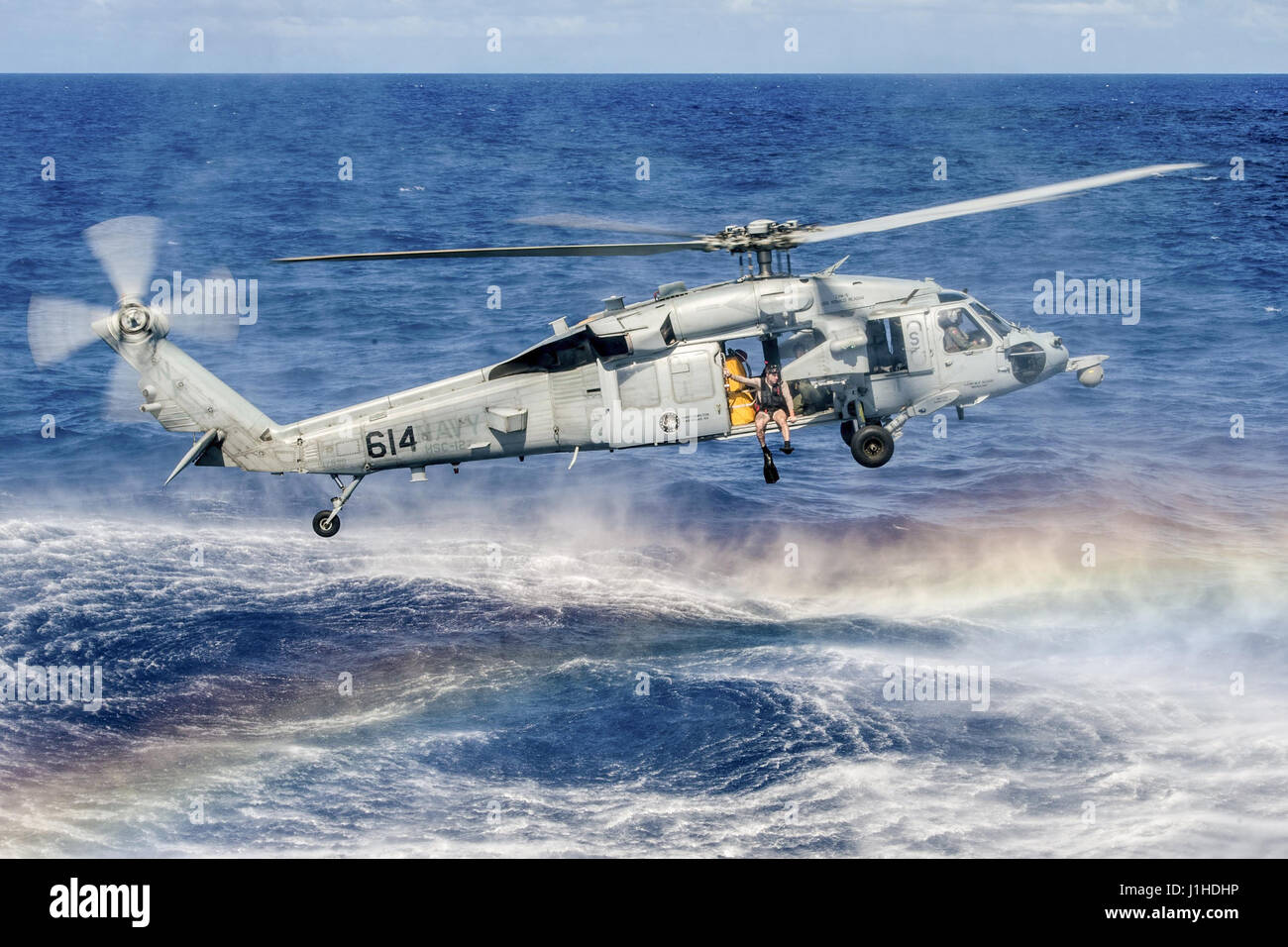Navy Officer prepares to jump from an MH-60S Seahawk during search and rescue training - Stock Image