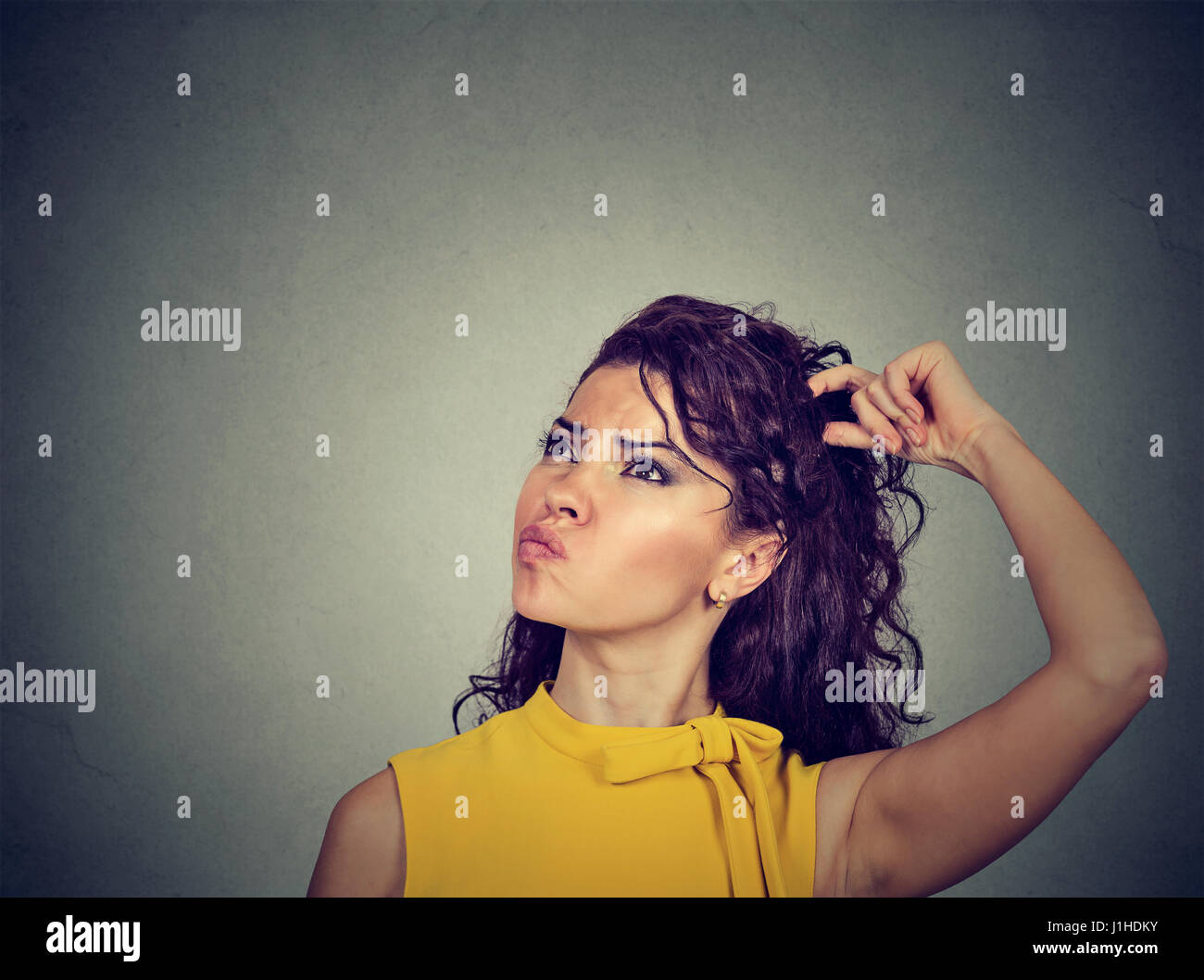 Portrait confused thinking young woman bewildered scratching her head seeks a solution looking up isolated on gray Stock Photo