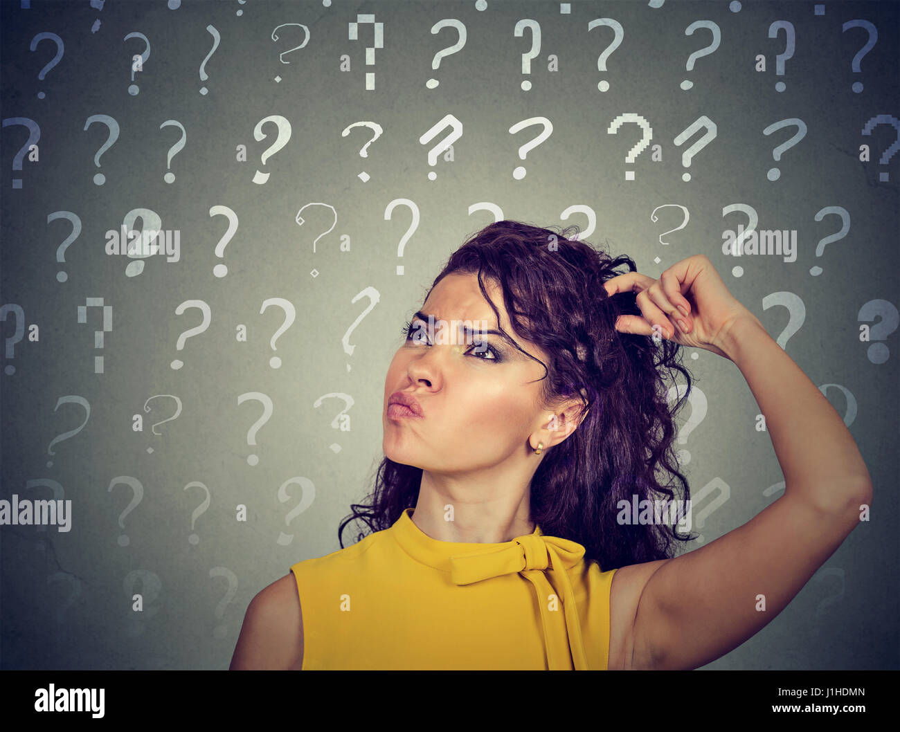 Portrait confused thinking young woman bewildered scratching her head seeks a solution looking up at many question - Stock Image