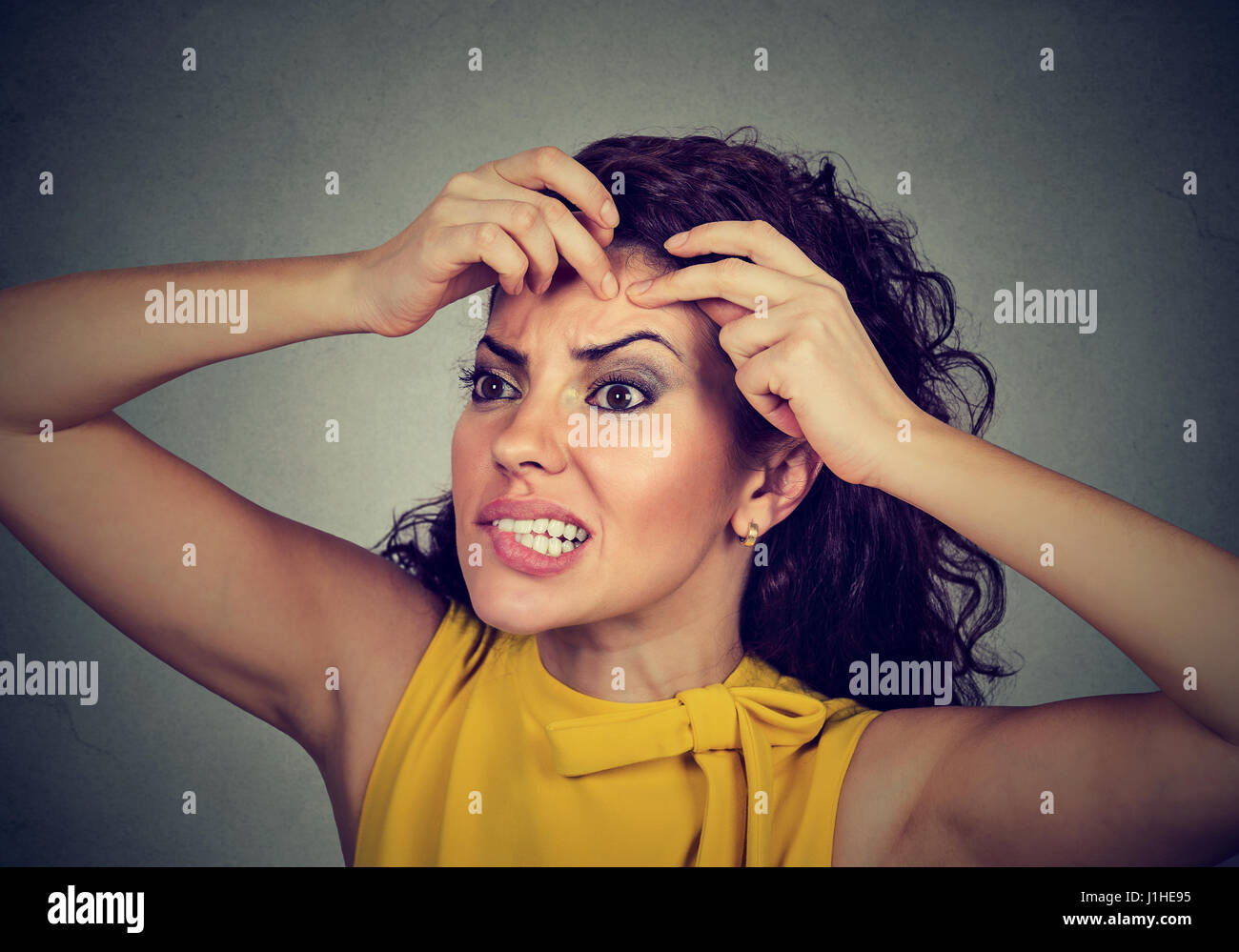 Closeup portrait of a woman looking in a mirror squeezing an acne or blackhead on her face forehead - Stock Image