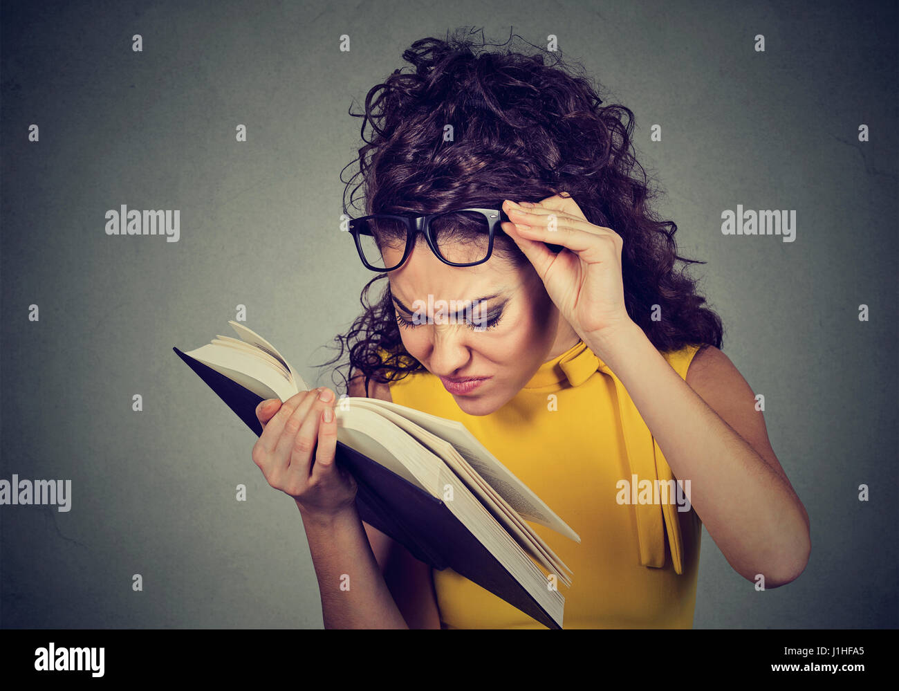 Young woman with glasses reading a book, having difficulties seeing text, has sight problems. Eyesight issues concept. - Stock Image