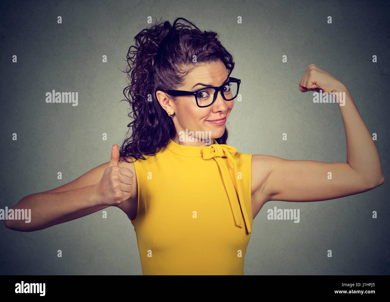 Young happy woman flexing muscles showing thumbs up isolated on gray background. Positive emotion facial expression. - Stock Image