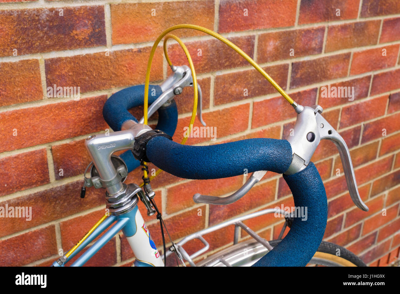 Bicycle with padded classic drop handlebars leaning up against a brick wall. UK - Stock Image