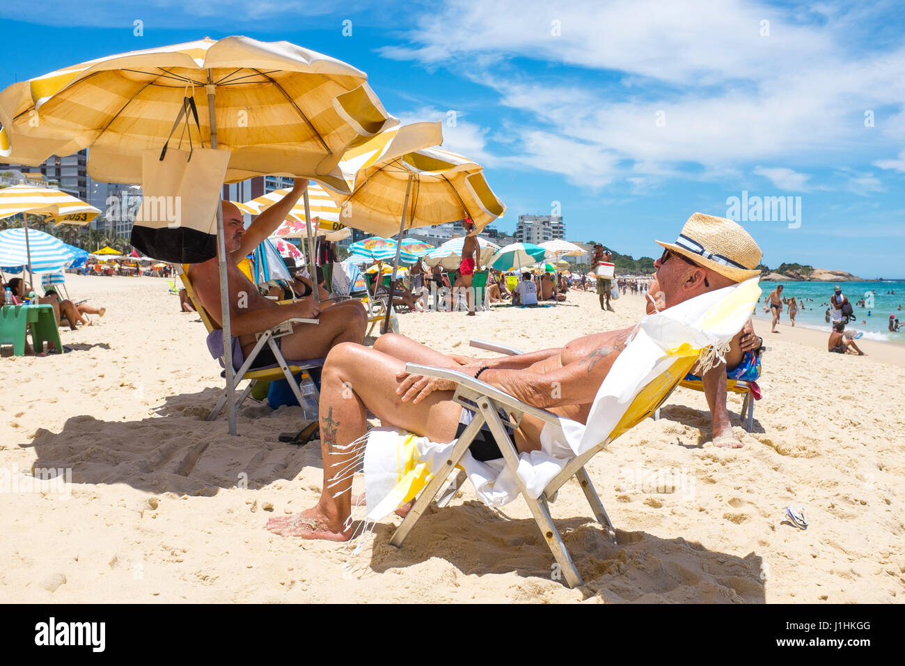 RIO DE JANEIRO - JANUARY 18, 2017: Beachgoers relax in and out of the shade of beach umbrellas on a hot summer afternoon - Stock Image