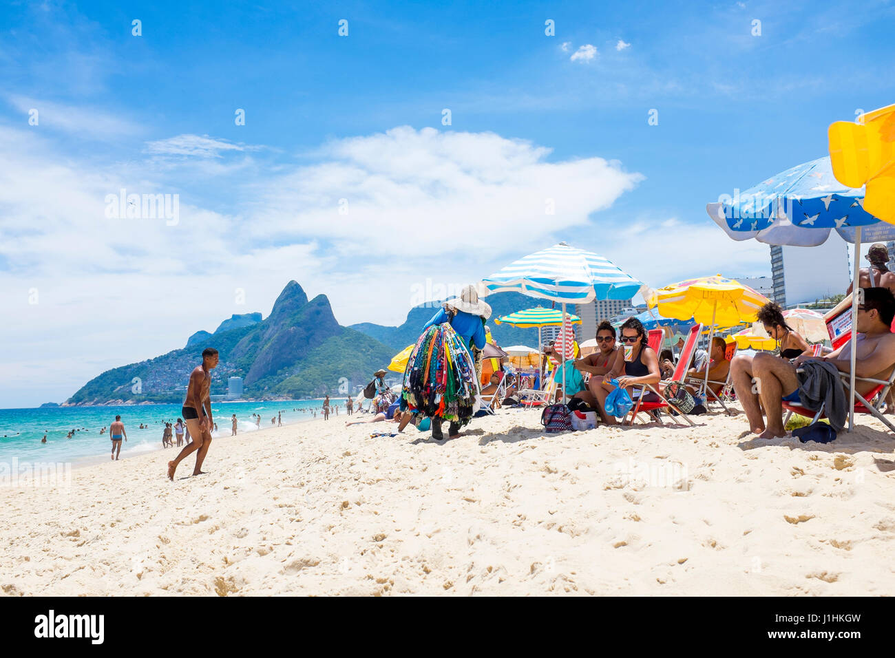 RIO DE JANEIRO - JANUARY 18, 2017: Beach vendors pass beachgoers relaxing in the shade of umbrellas on a hot summer - Stock Image