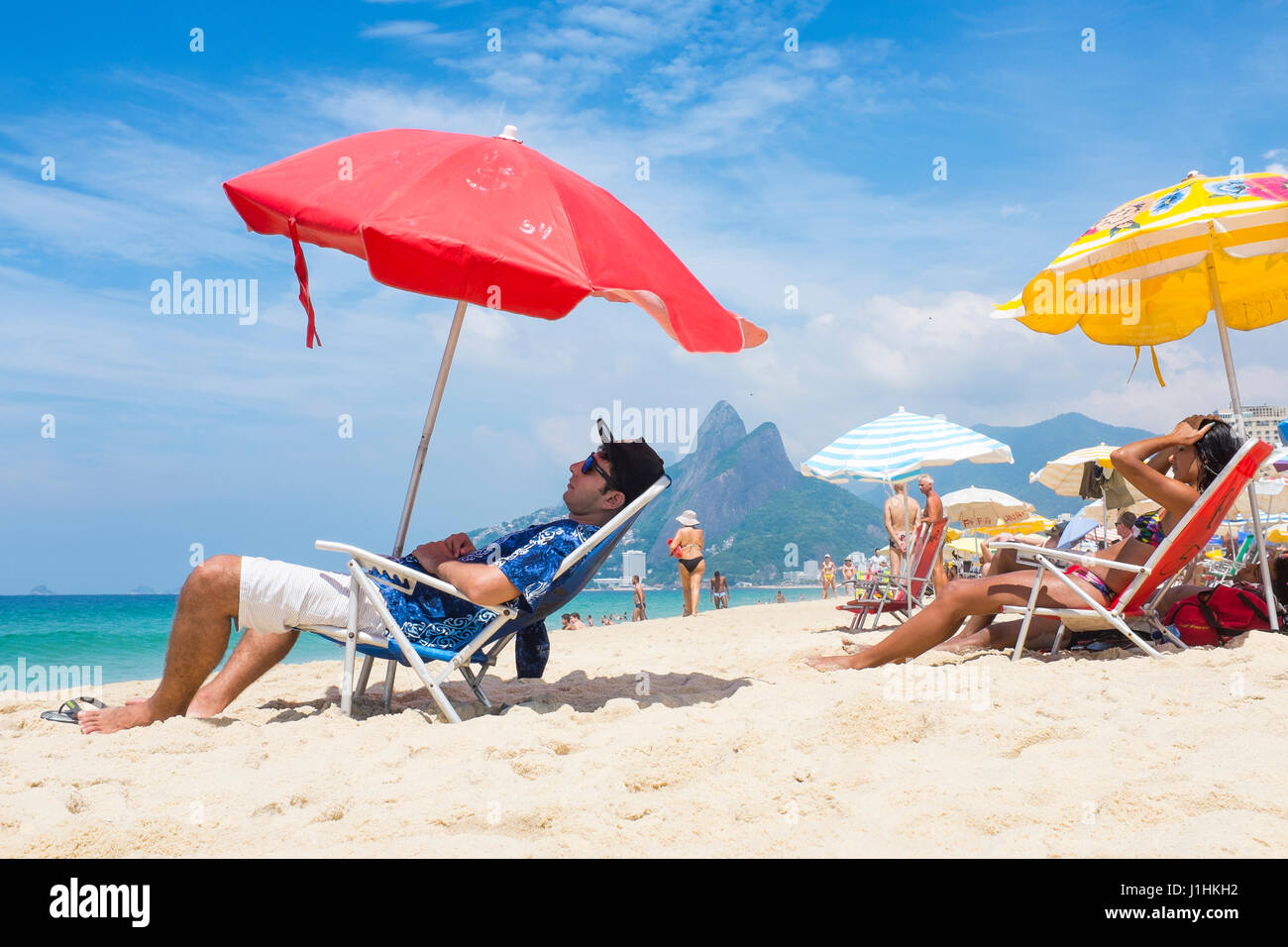 RIO DE JANEIRO - JANUARY 22, 2017: Beachgoers relax in the shade of beach umbrellas on a hot summer afternoon in - Stock Image