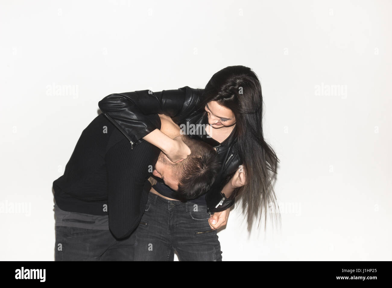 two people, young adult candid, brother sister, woman man, punching, white background - Stock Image
