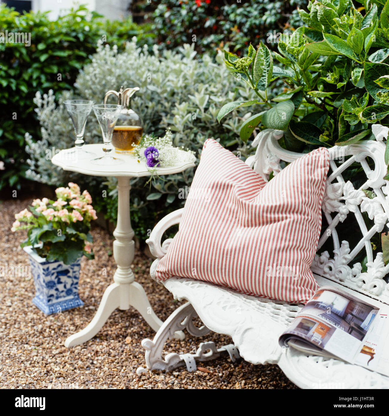 Striped cushion on bench. - Stock Image