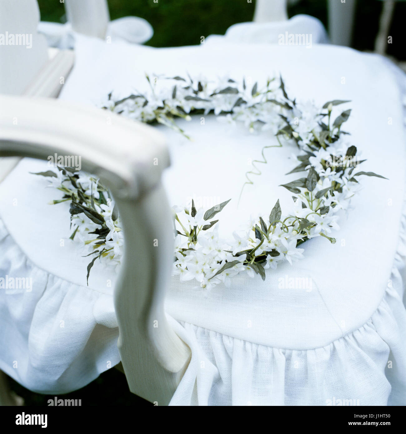 Wreath of white flowers on chair. - Stock Image