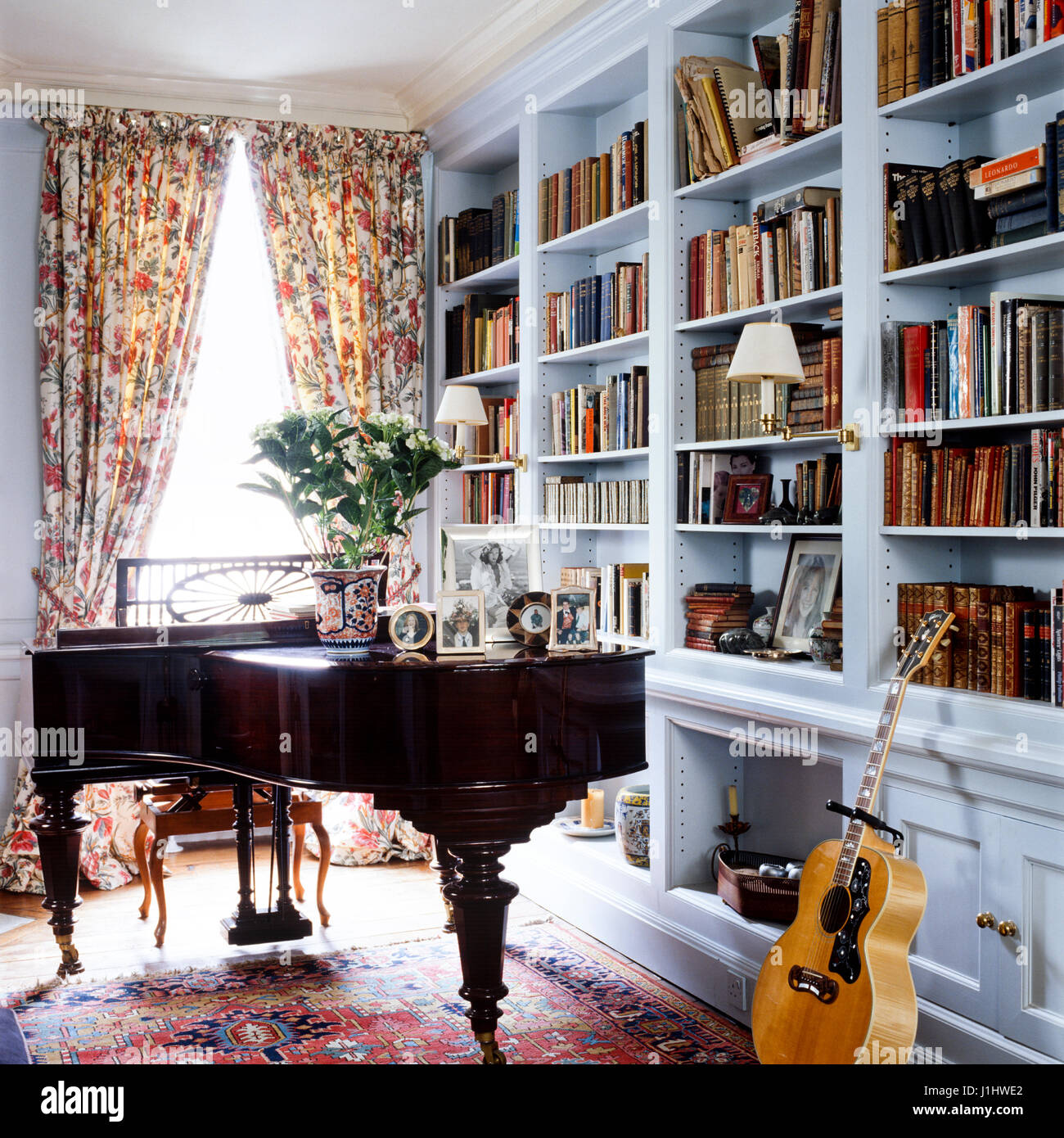 Piano and guitar beside bookshelf. - Stock Image