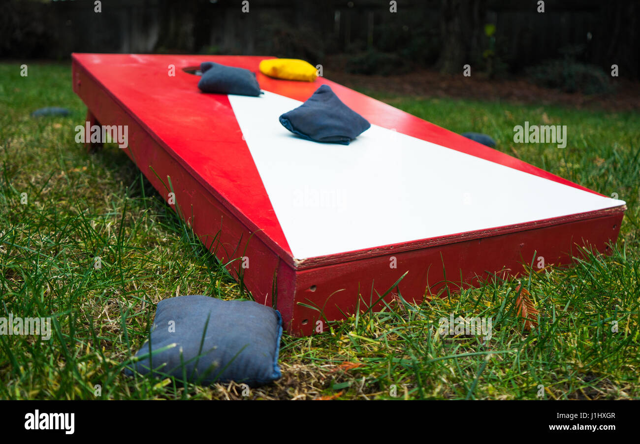 Red and white cornhole board toss game with beanbags on grass in garden - Stock Image