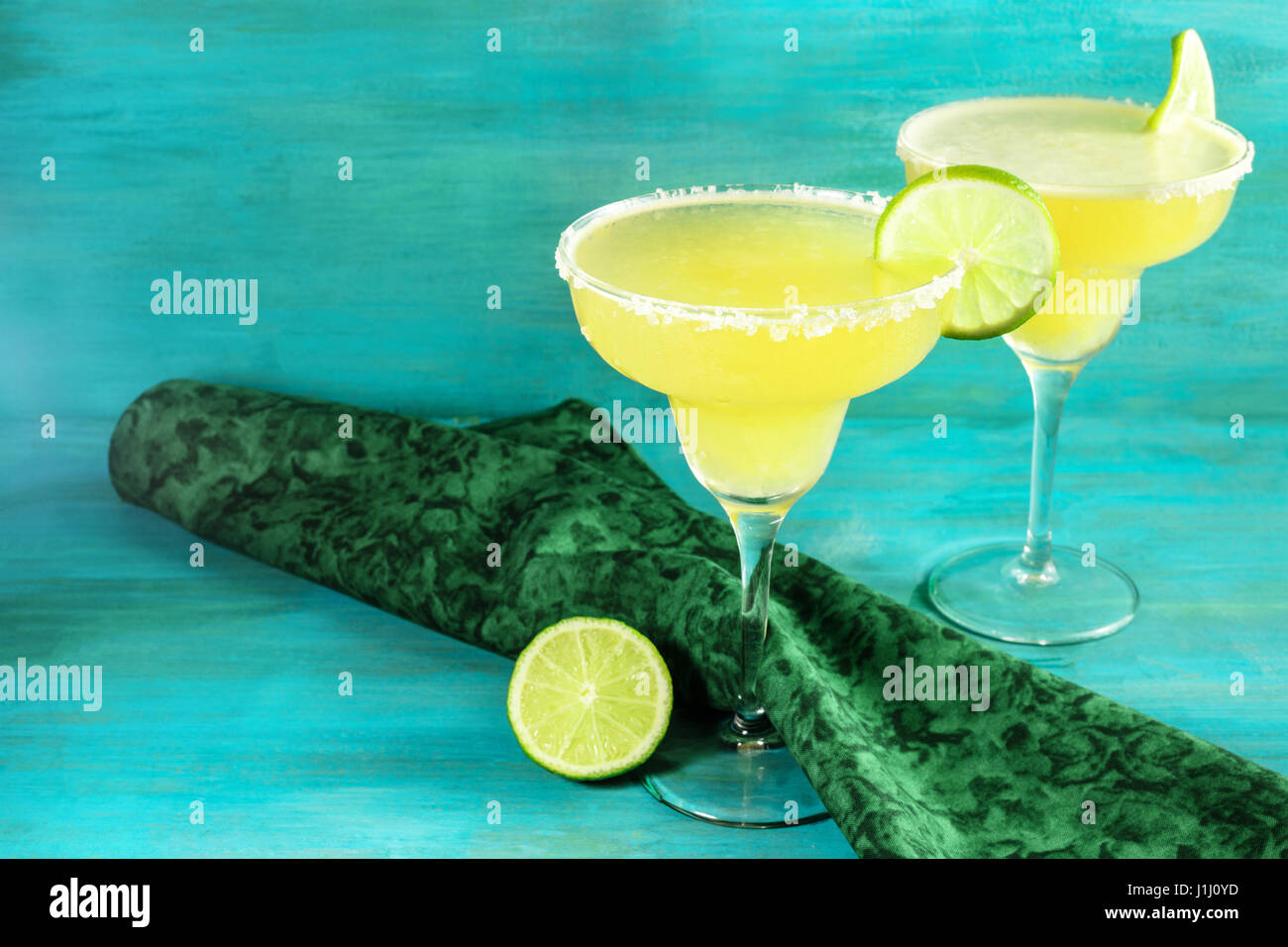 Lemon Margarita cocktails with limes and copyspace - Stock Image