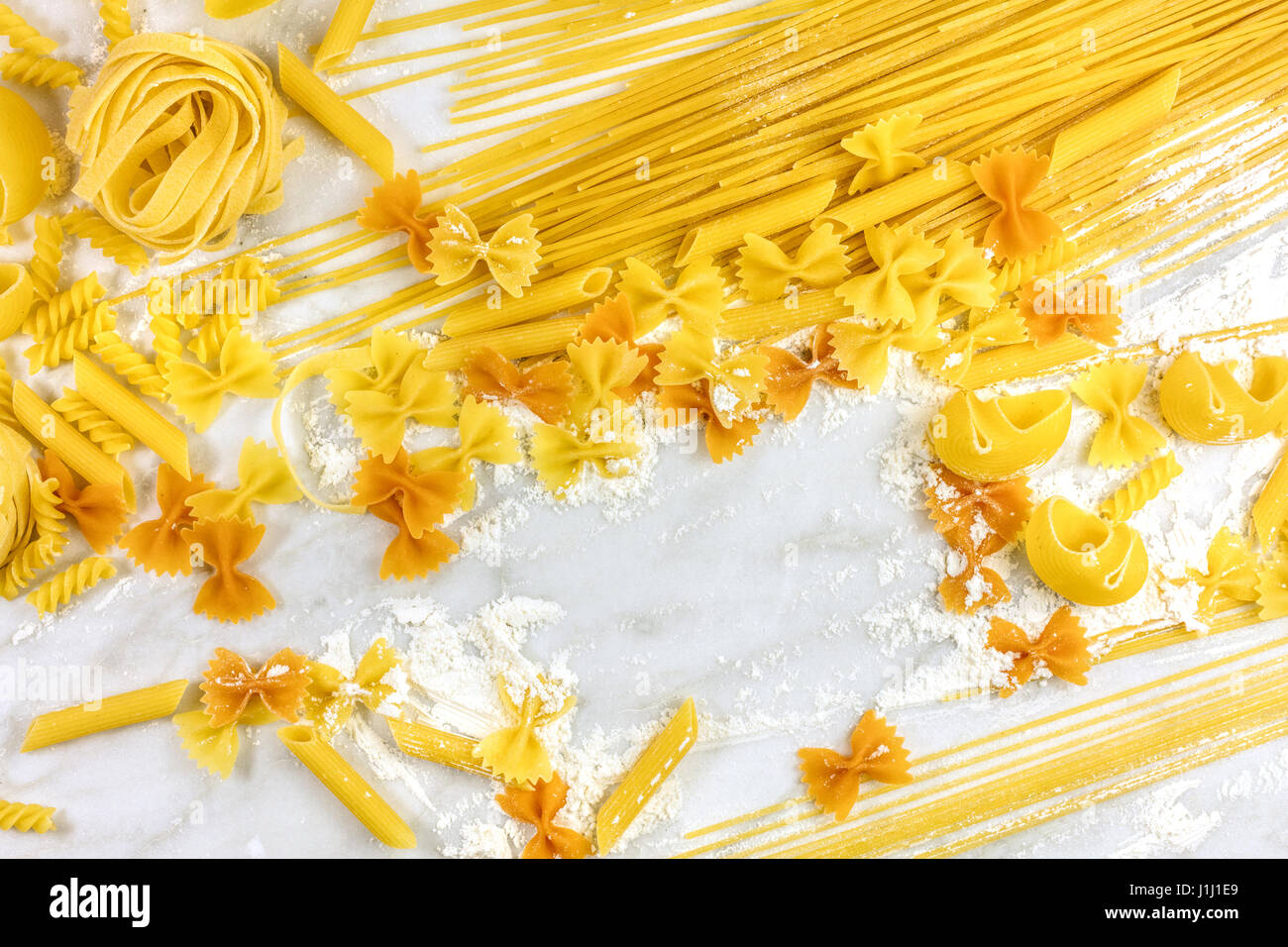 Various types of pasta with flour and copyspace - Stock Image