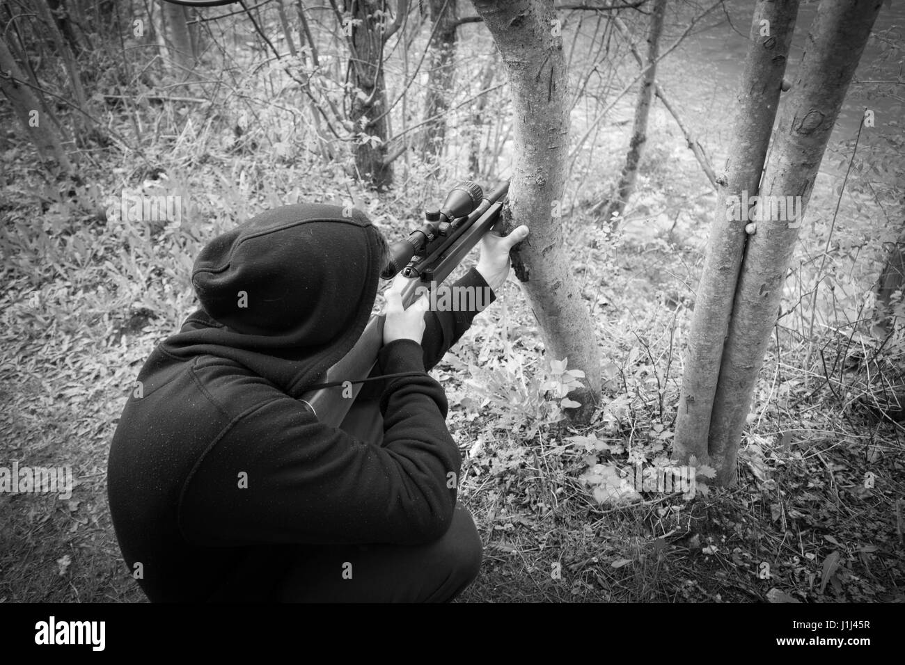Close-up of man in headgear aiming with sniper rifle - Stock Image