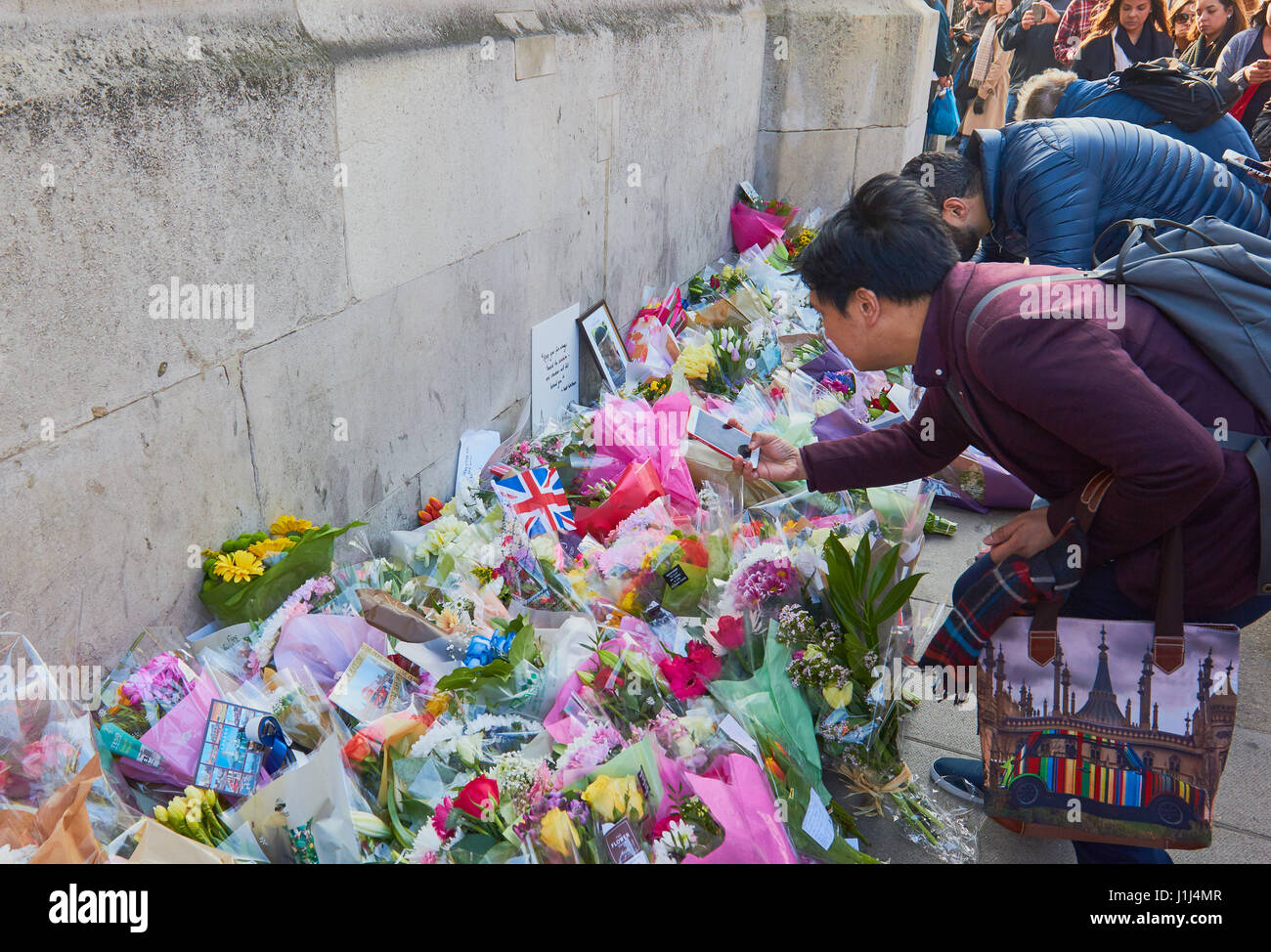 Tourists looking at floral tributes to victims of the Westminster terrorist attack, London, England - Stock Image