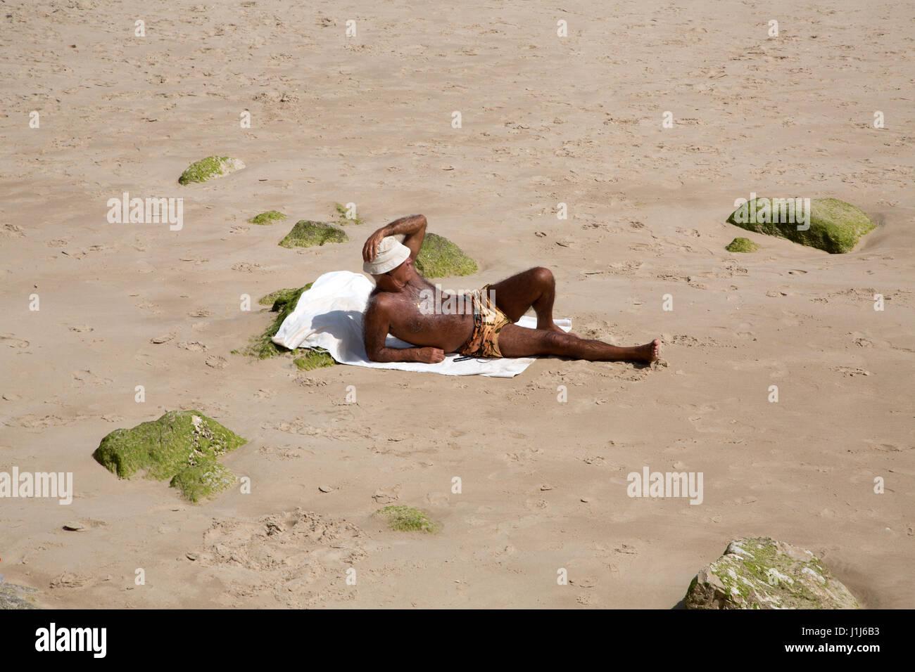 An older man sunbathing on Cascais beach, Lisbon, Portugal. - Stock Image