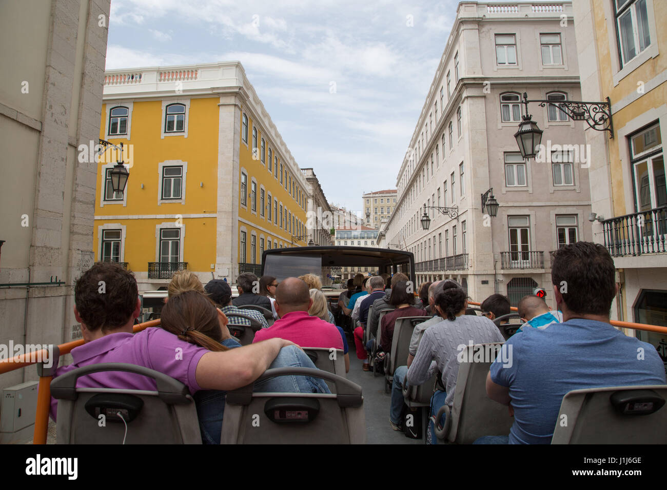 Tourists ride an open top bus in Lisbon, Portugal. Stock Photo