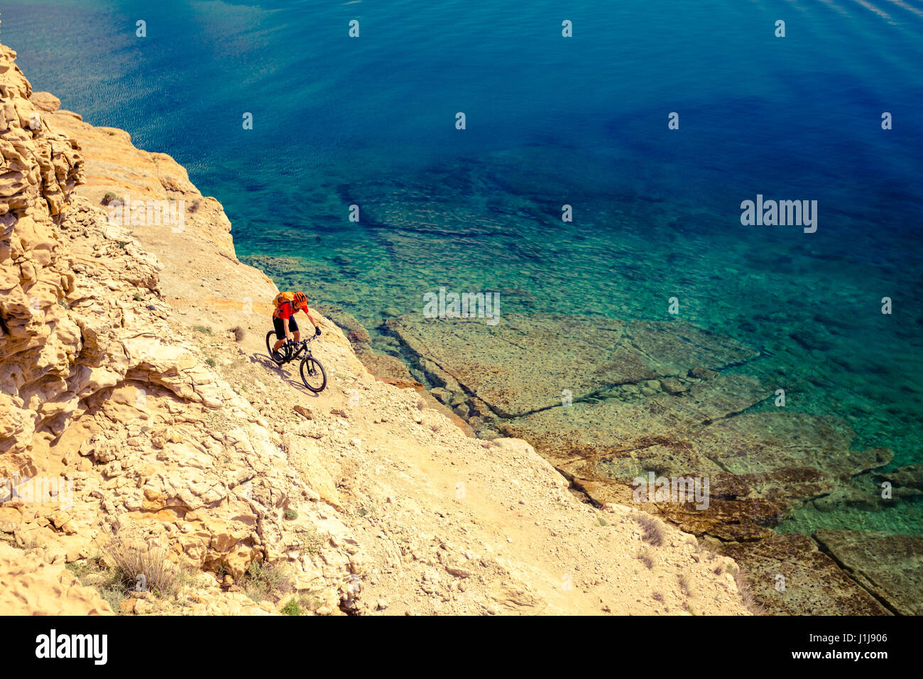 Mountain biker riding on bike in summer inspirational mountains and sea landscape. Man cycling MTB on enduro trail - Stock Image