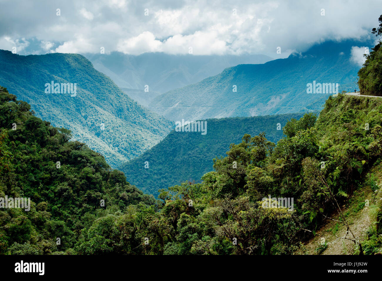 Panoramic view of the mountainous landscape of North Yongas and a cyclist on the Death Road on the far right, Bolivia - Stock Image
