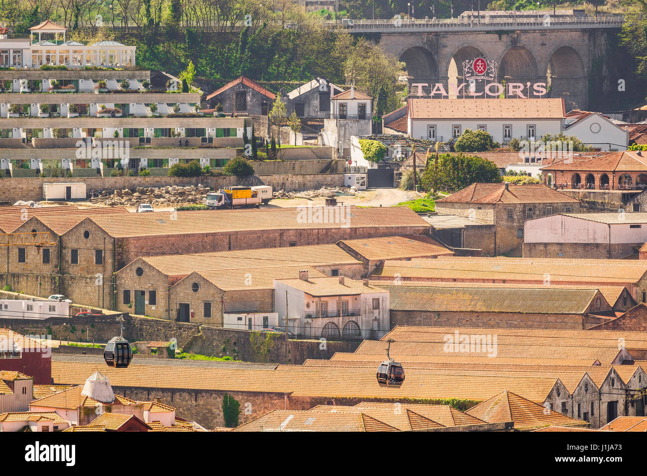 Porto Portugal Gaia, cable cars carrying tourists pass over the rooftops of port wine lodges sited in the waterfront - Stock Image